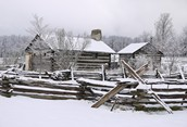 Early snow on log house